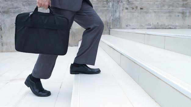 Die füße eines geschäftsmannes. tragen sie eine tasche in der hand und steigen sie die treppe hinauf, um in der firma zu arbeiten. menschen lebensstil erfolgreich und wettbewerbskonzept