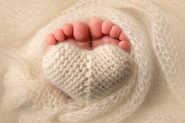 Die füße eines neugeborenen sind in eine gestrickte decke gehüllt. die finger eines neugeborenen babys halten ein weißes gestricktes herz. foto in hoher qualität
