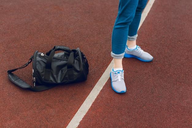 Die füße in grauen turnschuhen stehen in der nähe der weißen linie auf dem stadion. in der nähe befindet sich eine schwarze sporttasche.