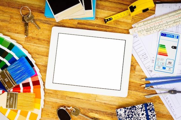 Die funktionierende desktop-flat-lay-szene des innenarchitekten mit dem architekturplan des hauses, dem farbführer und den pinseln