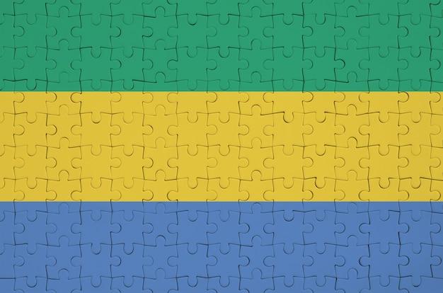 Die gabunische flagge ist auf einem gefalteten puzzle abgebildet