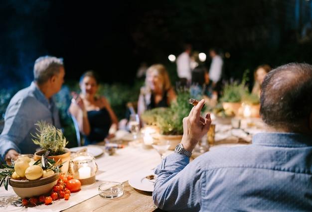 Die gäste sitzen am gedeckten tisch und kommunizieren miteinander