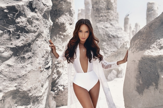 Die gebräunte sexy junge frau mit bilden und tragende weiße kleidung des sommers des dunklen haares, die nahe weißen felsen aufwirft