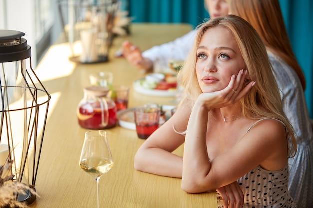 Die gelangweilte kaukasische frau sitzt allein im restaurant