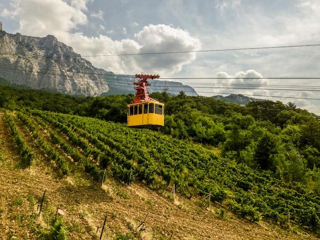 Die gelbe kabinenseilbahn befördert die menschen während der sommersaison zum gipfel.