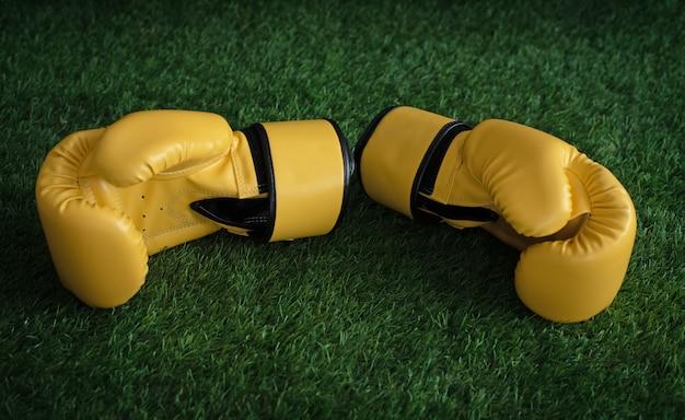 Die gelben boxhandschuhe setzen auf grünes gras im erdgeschoss und verschwommenes licht