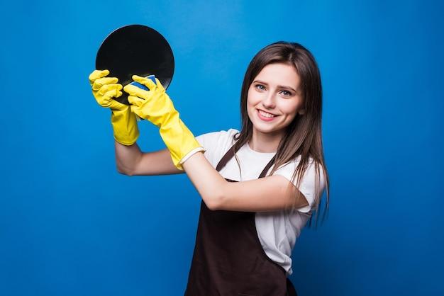 Die gelben gummihandschuhe der jungen hausfrau halten einen weißen teller und einen schwamm