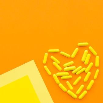 Die gelben süßigkeitskapseln, die herz bilden, formen auf orange hintergrund