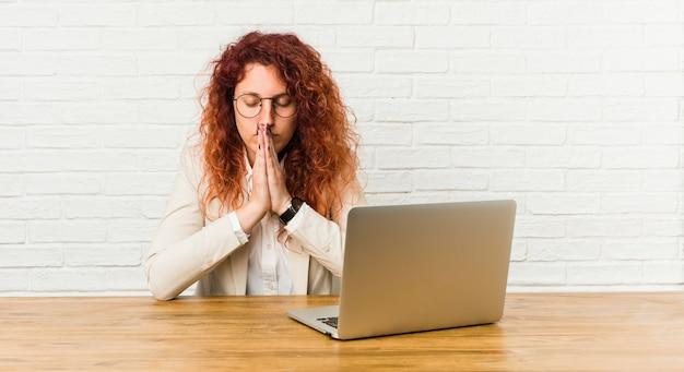 Die gelockte frau der jungen rothaarigen, die mit ihrem laptophändchenhalten arbeitet, beten herein nahe mund, fühlt sich überzeugt.