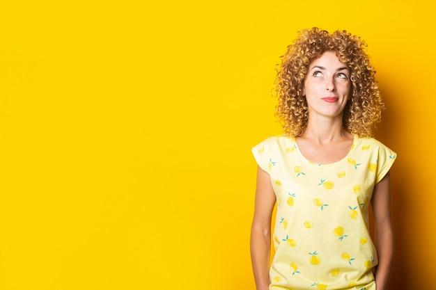 Die gelockte junge frau schaut nachdenklich auf einem gelben hintergrund auf