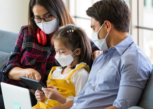 Die gemischte familie bleibt zusammen mit einer hygieneschutzmaske im gesicht zu hause