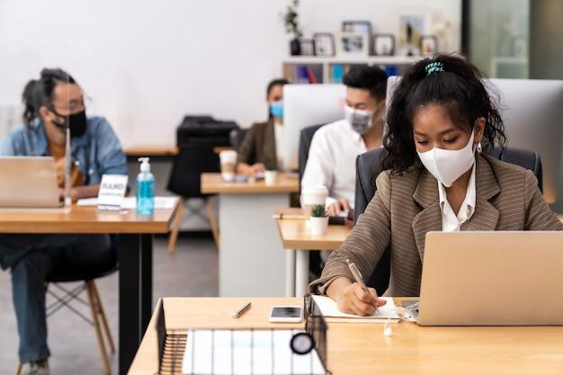 Die gemischte rasse der afrikanischen schwarzen und asiatischen geschäftsfrau trägt eine gesichtsmaske, die in einem neuen normalen büro mit sozialer distanz zu einer gruppe von geschäftsteammitgliedern arbeitet, um die ausbreitung des coronavirus covid-19 zu verhindern