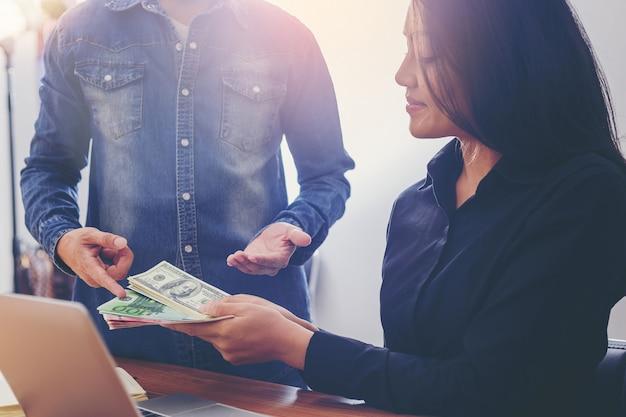 Die geschäftsfrau, die geld hält, erhält rat von ihrem kollegen, der geschäftsinvestition wählt.