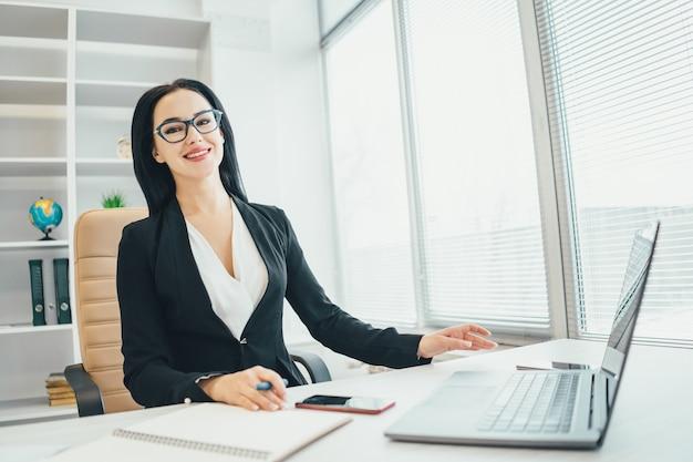 Die geschäftsfrau, die mit einem laptop am schreibtisch arbeitet