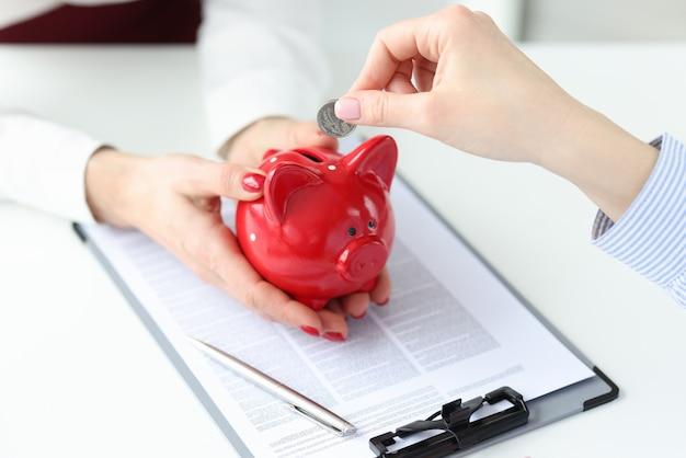 Die geschäftsfrau hält einen roten sparschwein-kunden in der hand, der münzen hineinsteckt
