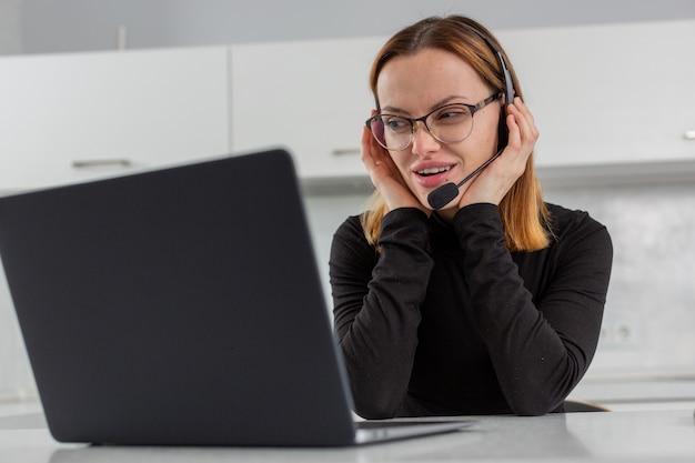 Die geschäftsfrau im headset schaut mit einem listigen blick auf den laptop-bildschirm und spricht über das webcam-callcenter-mitarbeiter-remote-arbeitsfoto in hoher qualität