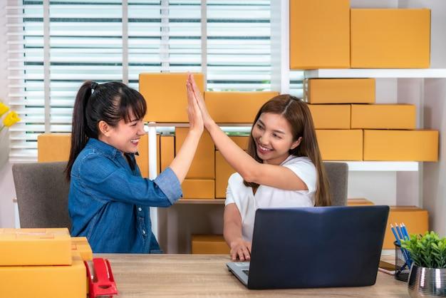 Die geschäftsfrau mit zwei asiaten des jugendlichinhabers arbeitet zu hause für das on-line-einkaufen und betrachtet und aufgeregt in der bestellung am laptop und mit büroausstattung, unternehmerlebensstilkonzept