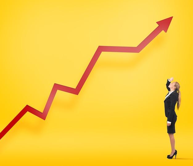 Die geschäftsfrau sieht zu, wie ihre unternehmensstatistik aufwächst. gelber hintergrund