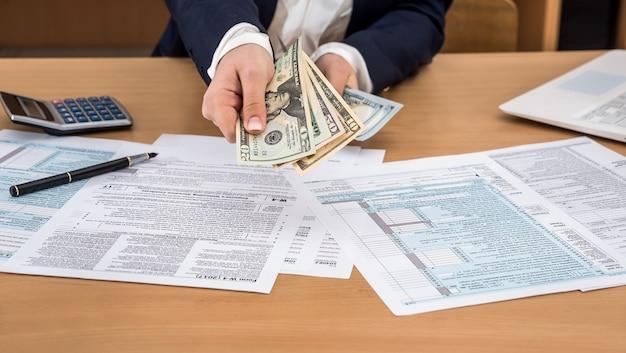 Die geschäftsfrau zählt dollars über dem steuerformular 1040