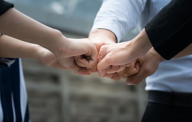 Die geschäftsleute, die hände sich verbinden, zeigen teamwork