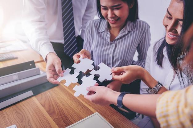 Die geschäftsleute, die setzen, schließen puzzle an. teamarbeit und strategisches lösungskonzept.