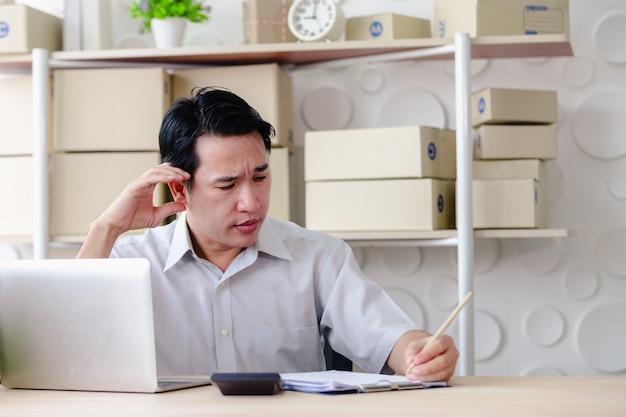 Die geschäftsmänner, die im büro schauen bildschirmlaptop sitzen, sind, kmu-kleinbetrieb ernst