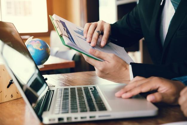 Die geschäftsmannhand, die diagrammdiagramm hält und diagrammdiagramm für zeigt, analysieren den verkaufsplan der firma im büro.
