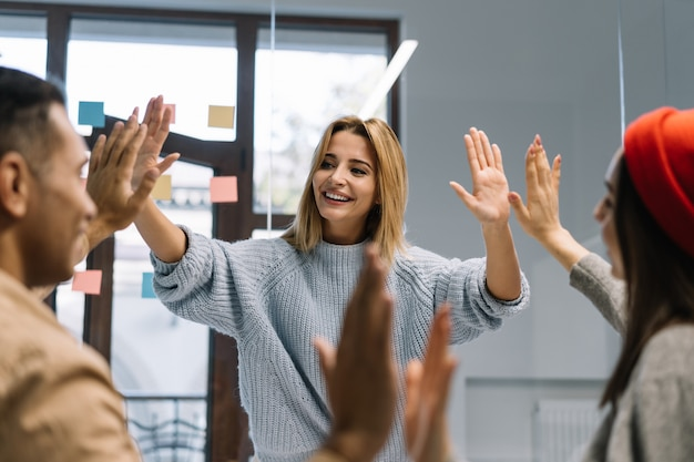 Die geschäftspartner der gruppe sind motiviert und geben high five, um erfolgreich zu feiern. treffen, teambuilding, erfolgreiches geschäft
