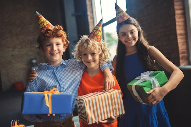 Die geschenke. drei freunde in bday hüten, die geschenke halten