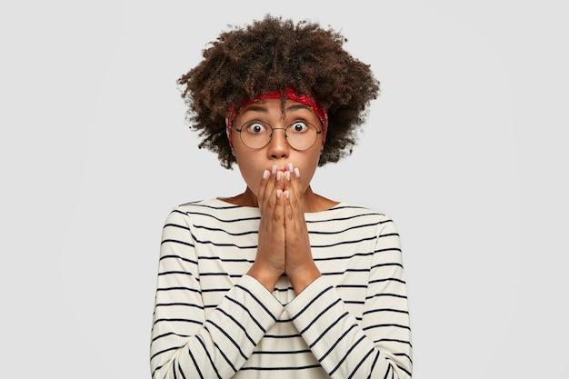Die geschockte afroamerikanische frau starrt mit abgehörten augen, bedeckt den mund mit handflächen, trägt freizeitkleidung, drückt überraschung aus und steht an der weißen wand. emotionales dunkelhäutiges mädchen