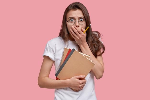 Die geschockte junge europäerin bedeckt den mund, blickt überrascht, trägt bleistift und notizbuch