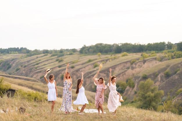 Die gesellschaft fröhlicher freundinnen hat eine tolle zeit zusammen auf einem picknick an einem malerischen ort mit blick auf die grünen hügel. mädchen in weißen kleidern tanzen auf dem feld