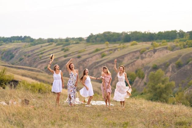 Die gesellschaft fröhlicher freundinnen vergnügt sich auf einem picknick an einem malerischen ort mit blick auf die grünen hügel. mädchen in weißen kleidern tanzen auf dem feld