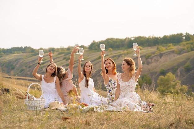 Die gesellschaft von freundinnen, die spaß haben und ein sommergrünes picknick genießen und gläser mit wein heben. menschen-konzept.