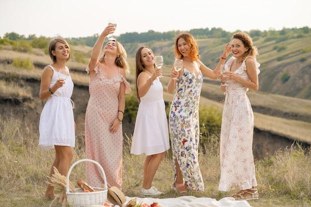 Die gesellschaft von wunderschönen freundinnen hat spaß und genießt ein sommergrünes picknick, tanzt und trinkt alkohol. menschen-konzept.