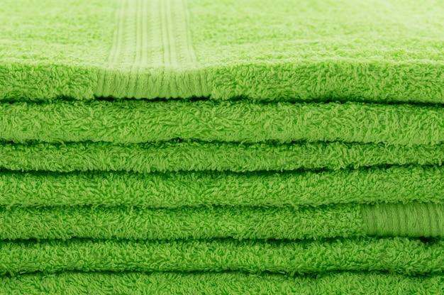 Die gestapelten grünen handtücher, ähnlich wie rasen mit grünem gras.