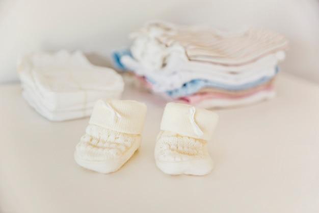 Die gestrickte socke des babys vor der windel und kleidung gestapelt