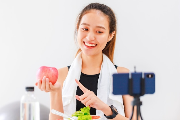Die gesunde bloggerin der schönen asiatischen frau zeigt apfelfrucht und sauberes diätnahrungsmittel. vor dem smartphone zur aufzeichnung von vlog-video-live-streaming zu hause.
