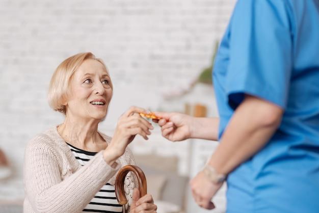 Die gesundheit unterstützen. bemerkenswerte fleißige kompetente frau, die einige vitamine der alten dame verschreibt, nachdem sie sie zu hause besucht und eine untersuchung durchgeführt hat