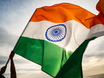 Die gewellte indische Flagge auf dem Sonnenunterganghimmel. Indischer Unabhängigkeitstag.