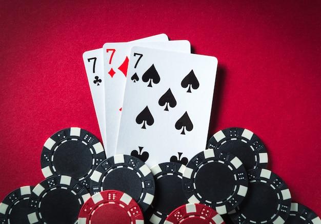 Die gewinnende pokerkombination ist drei arten oder sets. chips und karten am roten tisch im pokerclub