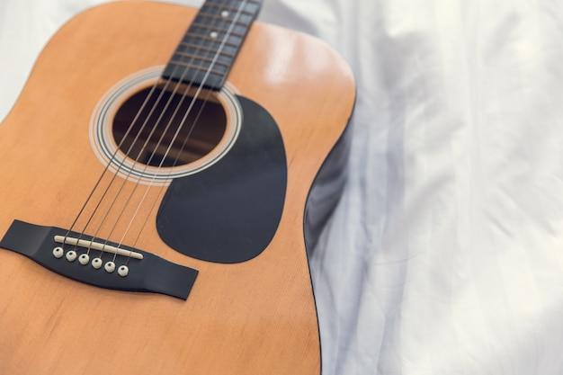 Die gitarre mit weißem betthintergrund, musik im schlafzimmermorgenkonzept.