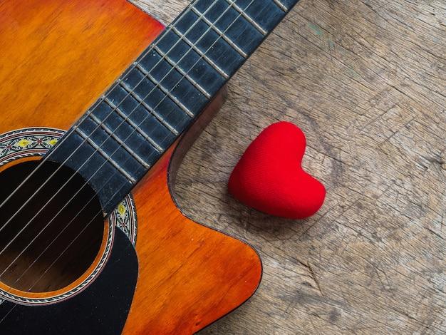 Die gitarre und rotes herz auf hölzernem beschaffenheitshintergrund