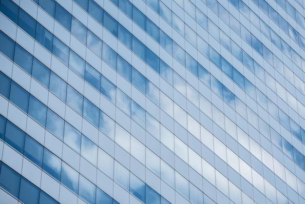 Die gläser, die beschaffenheitshintergrund mit errichten, reflektieren sich vom blauen himmel und von den wolken am vollen tag.