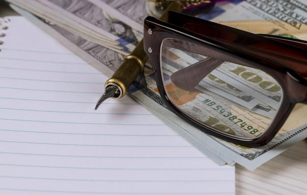 Die gläser im rahmen sind auf den dollars mit notizbuch und stift