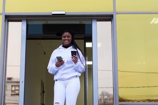 Die glückliche afroamerikanerin, die aus dem geschäftszentrum kommt