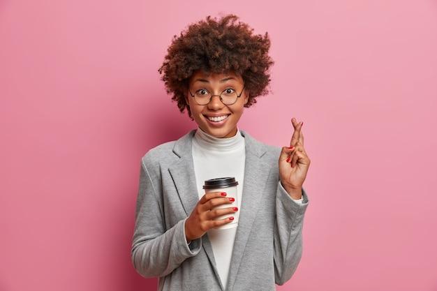 Die glückliche afroamerikanische geschäftsfrau drückt vor einem wichtigen ereignis die daumen, trinkt kaffee zum mitnehmen, setzt alle anstrengungen zum beten ein und hofft auf erfolg