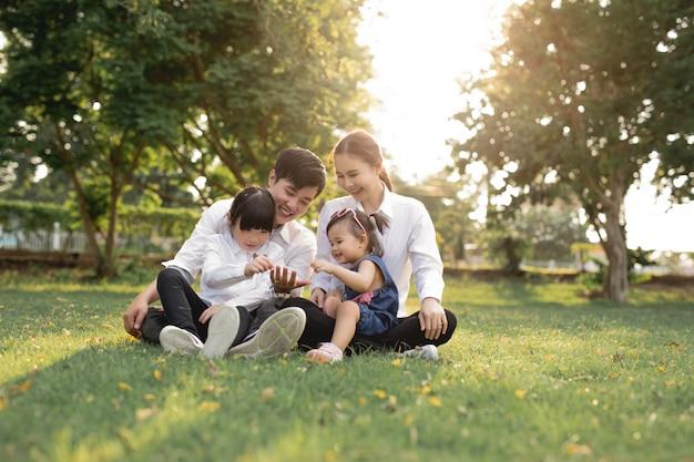 Die glückliche asiatische familie, die auf gras, eltern mit zwei kindern sitzt, lächeln.