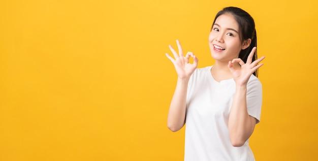 Die glückliche asiatische frau des porträts zeigt okes zeichen und betrachtet die kamera auf gelber wand.