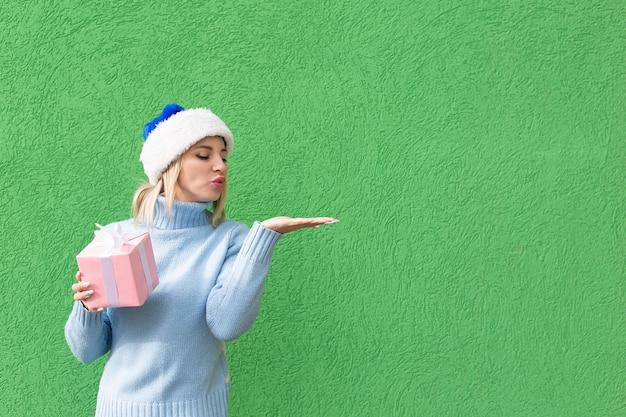 Die glückliche blondine in einem neujahrshut mit einem geschenk